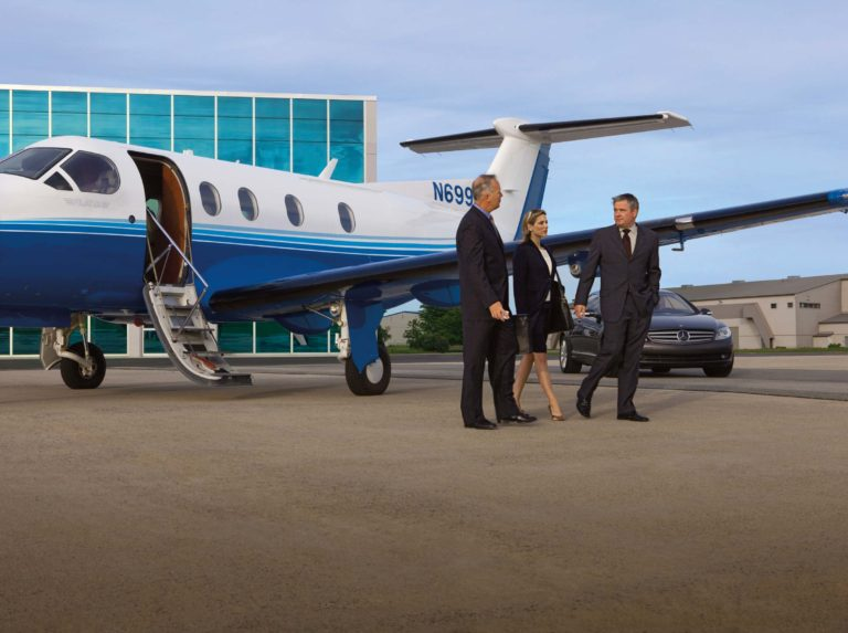 Pilots and flight staff standing near fractional jet ownership program aircraft