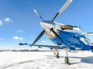 Pilatus aircraft at rest on snowy tarmac