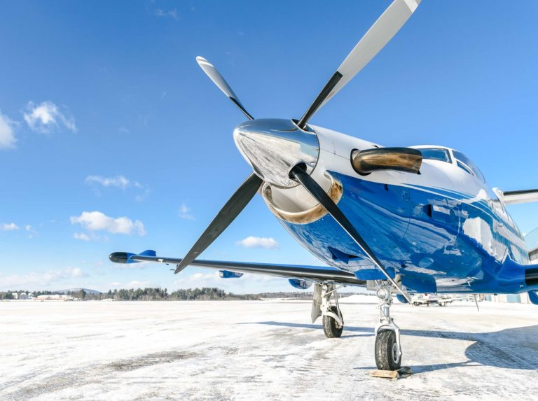 Pilatus aircraft at rest on snowy tarmac.