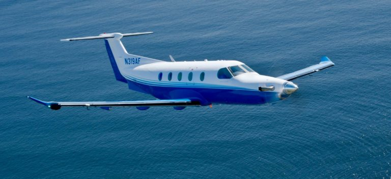 Pilatus PC-12 fractional aircraft ownership plane flying over water