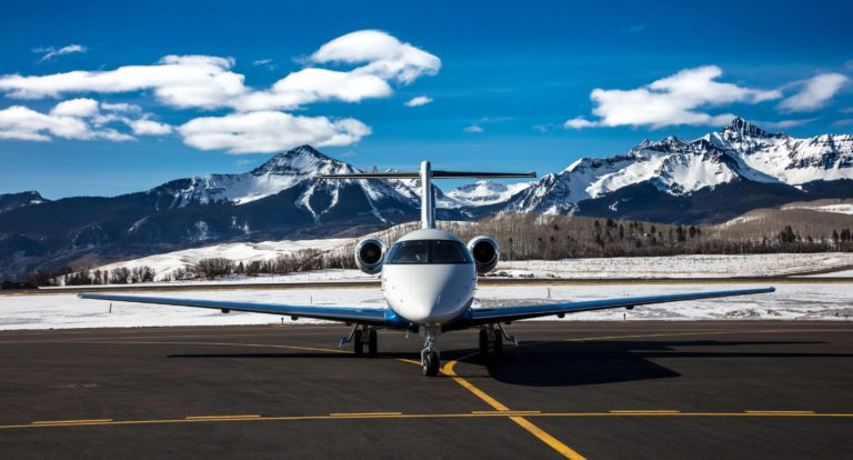 Pilatus PC-24 jet parked in front of snowy mountain