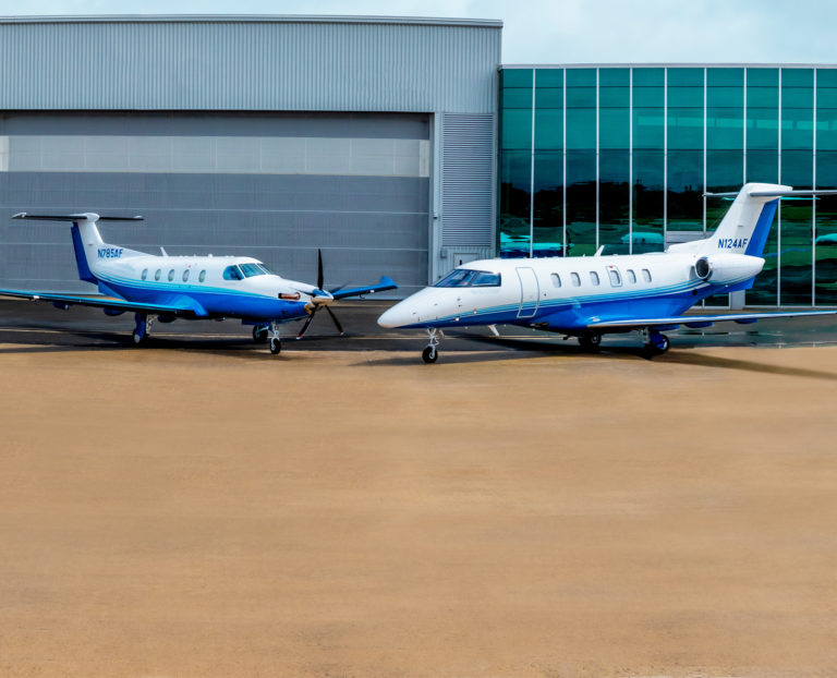 Executive travel aircraft Pilatus PC-12 and PC-24 parked in front of PlaneSense building