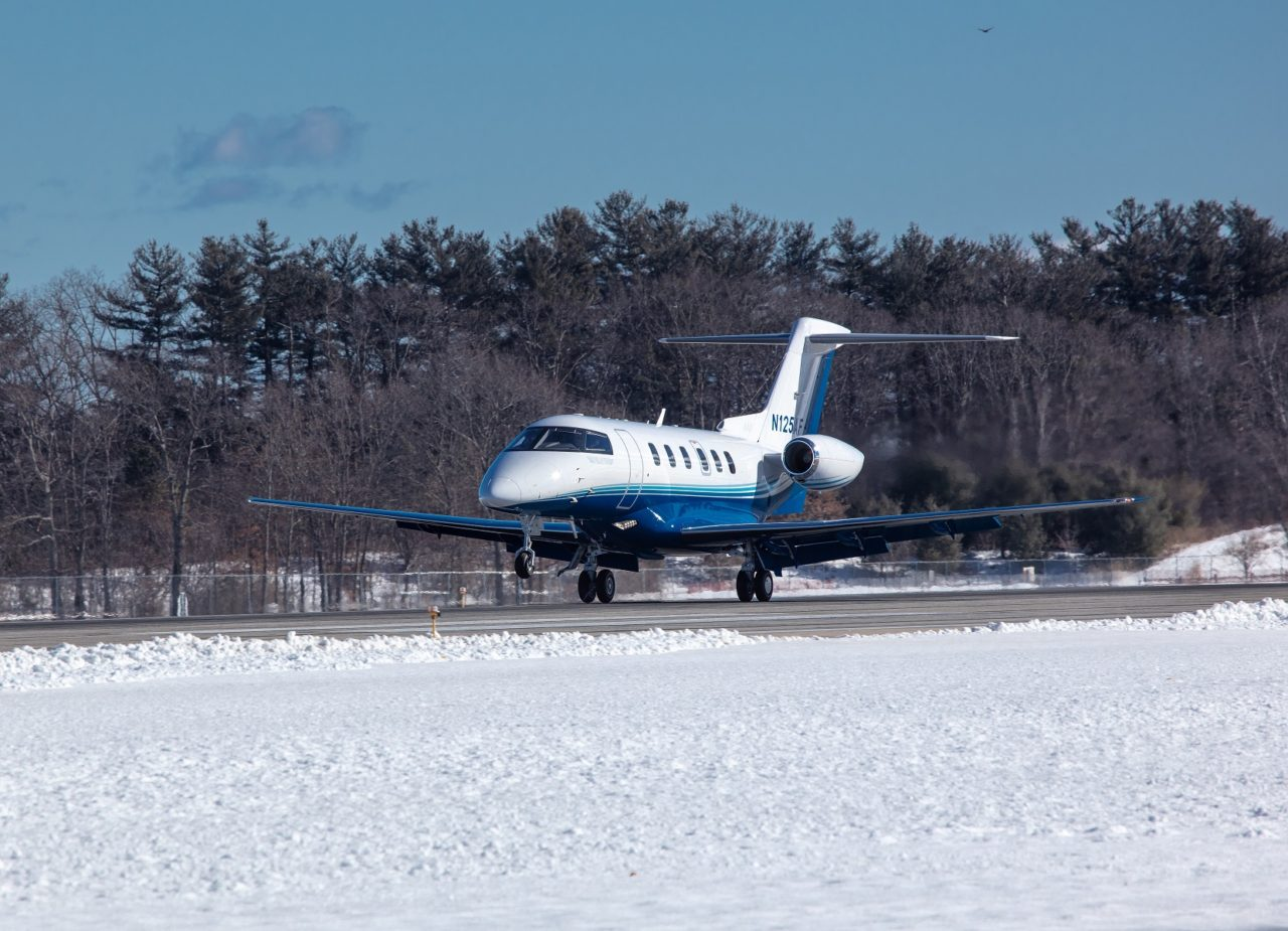 PlaneSense PC-24 jet landing on snowy runway.