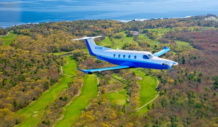 PlaneSense PC24 flying over fields