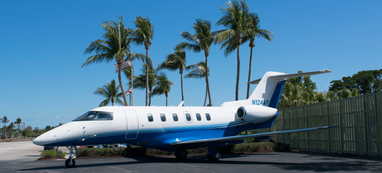 fractional jet program aircraft on the tarmac with palm trees